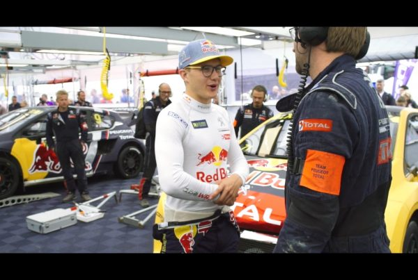 racing driver discussing car with pit team