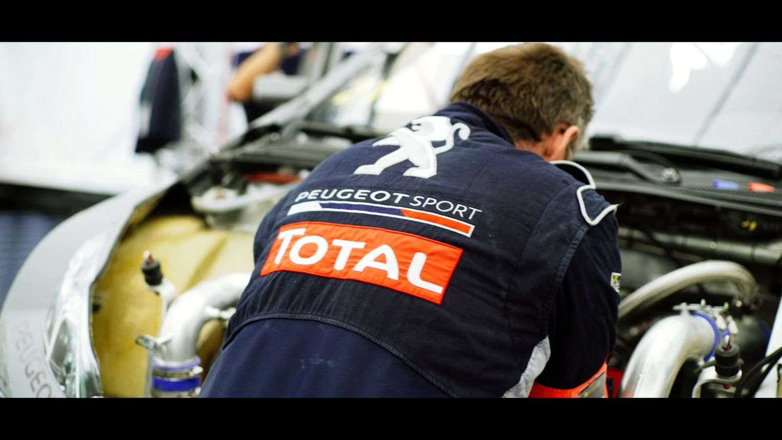 mechanic working on race car engine